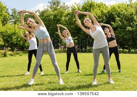 Turn right. Cheerful smiling young women turning aside and holding hands together while doing sport exercises outdoors,