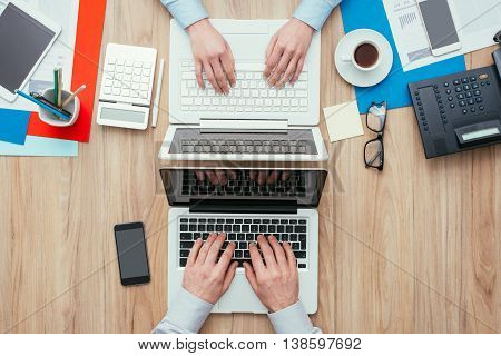 Man and woman working at office desk with customized different workspaces the woman's side is full and the man's side is clean and simple