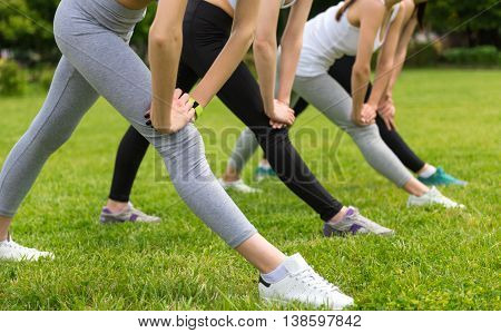 Pleasant morning. Nice slip sporty women stretching and doing exercises outdoors in the park