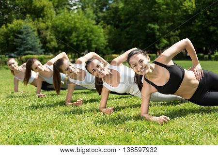 Live life fully. Cheerful smiling slim women sporty lying in the position on the grass and doing sort exercises in the park while expressing joy