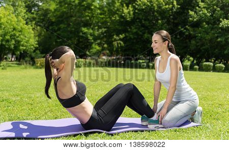 Strengthen your muscles. Pleasant slim smiling woman lying on the roll mat and working her abs while her friends holding her toes