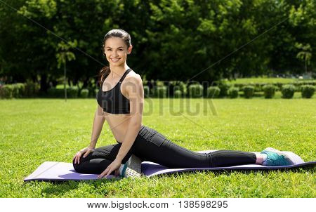 With positivity in mind. Pleasant joyful sporty slim woman stretching on the roll mat while doing sport exercises in the park