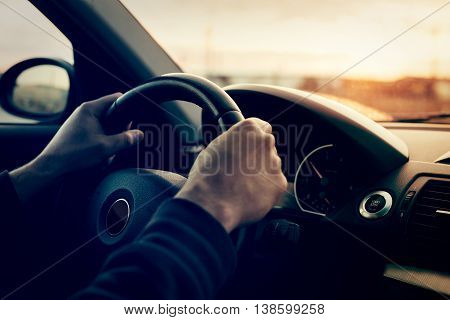 Driving a car at sunset - focus on steering weel