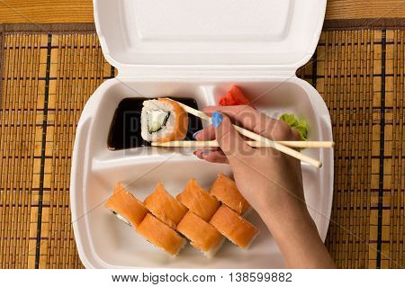 woman holding sushi rolls with salmon closeup
