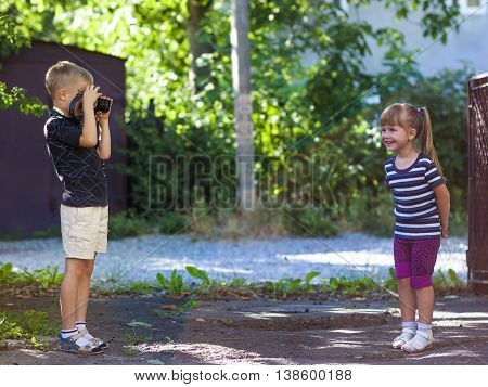 Little boy taking the picture of a litthe girl on sunny summer day
