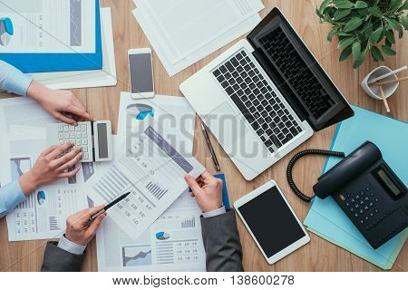 Business team working at office desk and analyzing financial reports finance and accounting concept top view