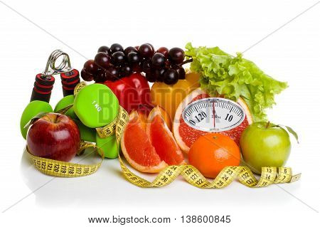 fitness equipment and healthy food isolated on white. green and red apples, pepper, grapes, grapefruit, parsley, nectarines, dumbbells and measuring tape