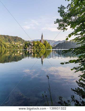 The Church of the Assumption on Bled Lake in the morning. Reflections can be seen in the water
