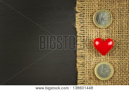 Old burlap on a black wooden board with valid euro coins.