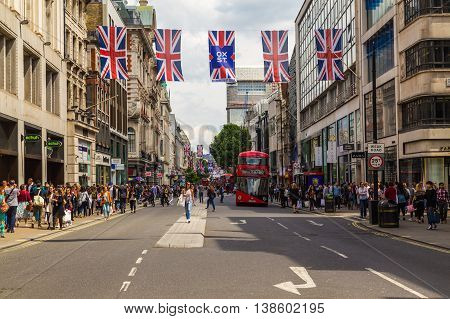 LONDON UK - 28TH JUNE 2016: A view along Oxford Street in London during the day. London Red double decker Buses union jack flags and lots of people can be seen.