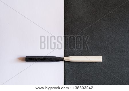 black and white crayons on alternate background of the same color to symbolize the differences and similarities tolerance or racism friendship or hatred