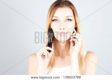 Smiling blonde woman touching face and holding professional brush for blush. Make up artist.