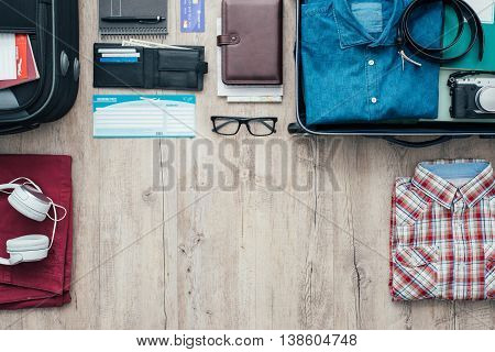 Getting ready for a trip and packing a suitcase before leaving; accessories clothing and personal items on a desktop travel and vacations concept
