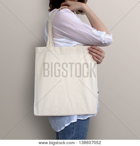 Girl is holding blank cotton eco bag design mockup. Handmade shopping bag for girls.