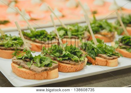 a plate of sandwiches and stuffing on a toothpick baguette, beef and lettuce.