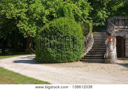 Stone stairway of a castle with wrought iron banister in a beautiful park.