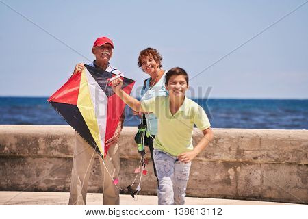 Family Boy And Grandparents Flying Kite Near Sea