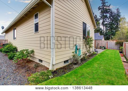 House Exterior With Beige Siding. Fenced Back Yard With Green Lawn.