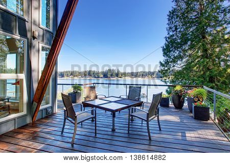 Large Covered And Furnished Porch Of Luxury House With View Of The Lake