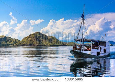 A boat approaches among the islands of Indonesia