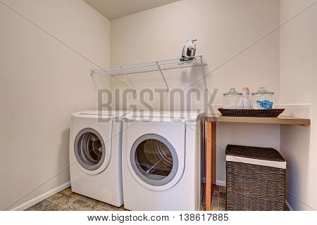 Small Laundry Room With White Appliances And Wicker Basket