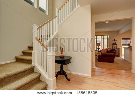 Bright Hallway In Creamy Tones With Hardwood Floor And Staircase