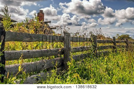 Old rustic wooden fence and the ruins of a brick chimney of destroyed hut in an overgrown field under the sky with cumulus clouds on a sunny day. Selective focus.