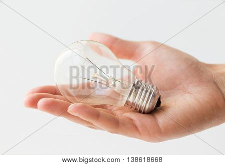 recycling, electricity, environment and ecology concept - close up of hand holding lightbulb or incandescent lamp