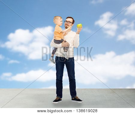 family, childhood, fatherhood, healthy eating and people concept - happy father and and little son with green apple over blue sky and clouds background
