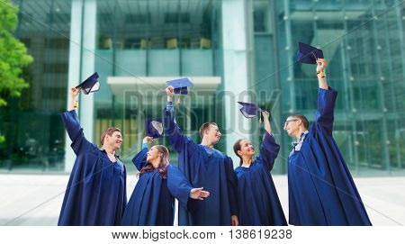 education, graduation and people concept - group of smiling students in gowns waving mortarboards over school or university building background