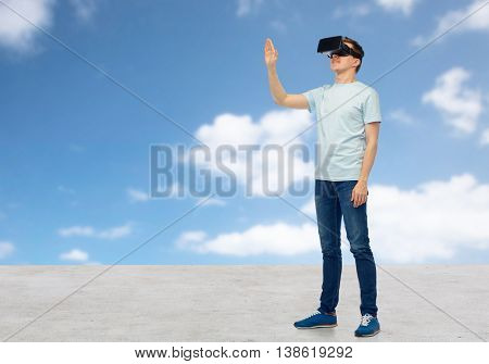 3d technology, virtual reality, entertainment, cyberspace and people concept - happy man with virtual reality headset or 3d glasses playing game and touching something over sky and clouds background