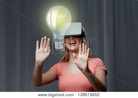 technology, virtual reality, entertainment and people concept - happy young woman with virtual reality headset or 3d glasses playing game at home looking at light bulb projection