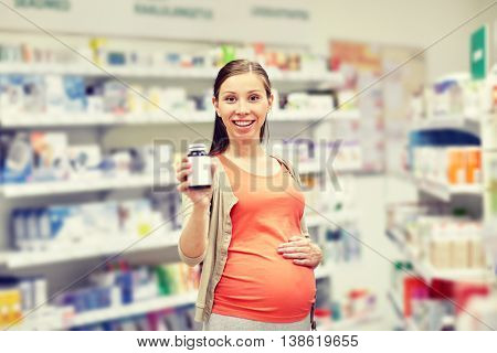 pregnancy, medicine, pharmaceutics, health care and people concept - happy pregnant woman showing medication jar at pharmacy