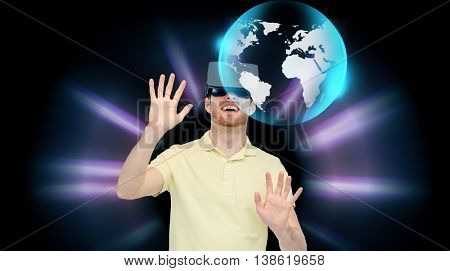 3d technology, virtual reality, cyberspace, entertainment and people concept - happy man with virtual reality headset or 3d glasses playing game and looking at globe projection over black background