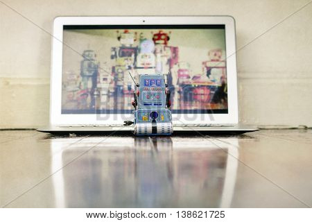 lone blue robot toy watching a laptop computer