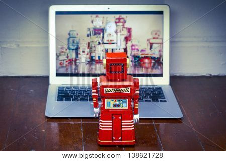 red robot toy watching  a laptop computer