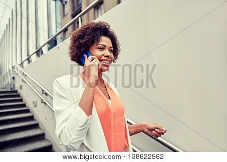 business, communication, technology and people concept - young smiling african american businesswoman calling on smartphone going down stairs into city underpass