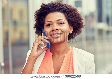 business, communication, technology and people concept - young smiling african american businesswoman calling on smartphone in city