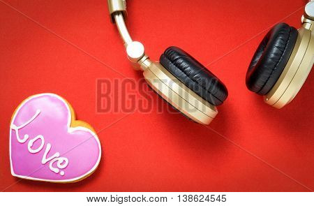 Love Heart on red background with Golden headphone.