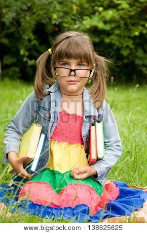 clever little pupil in glasses holding a book