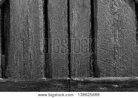 Wood and tar texture on some plank. Black wooden wall in bright sunshine. Recently tarred. BW, HDR-toning.