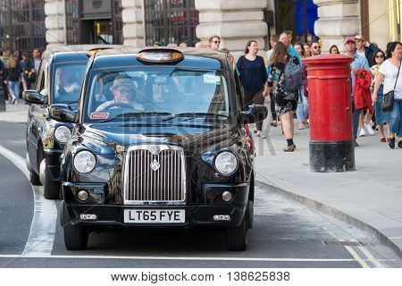 London, England - July 5, 2016: Typical black London cab in central London with United kingdom flags in the background