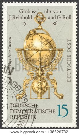 MOSCOW RUSSIA - CIRCA FEBRUARY 2016: a post stamp printed in DDR shows globe clock by Reinhold and Georg Roll the series