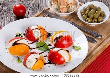 tomato. mozzarella basil caprese summer salad with dressing close-up