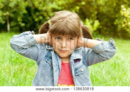 young girl closed her ears with her hands. concept