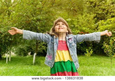 little girl happily raised her hands up