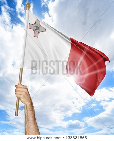 Person's hand holding the Malta national flag and waving it in the sky, 3D rendering