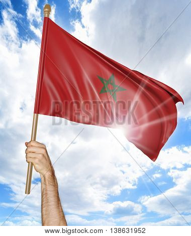 Person's hand holding the Moroccan national flag and waving it in the sky, 3D rendering