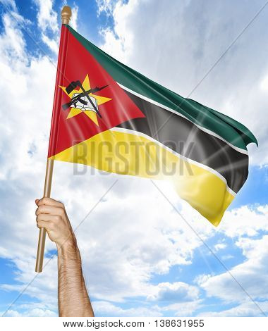 Person's hand holding the Mozambican national flag and waving it in the sky, 3D rendering