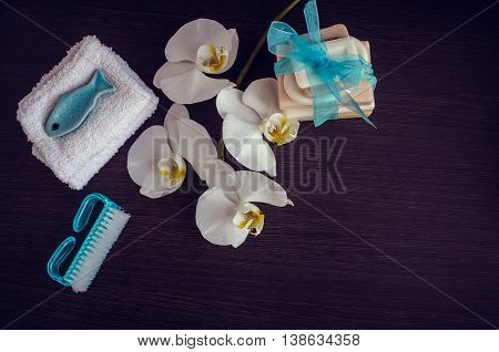 Spa setting in purple and blue colors with different kind of natural soaps, soft towels and orchid on dark wooden background. Tower stack of different handmade soaps. Selective focus. Copy space.